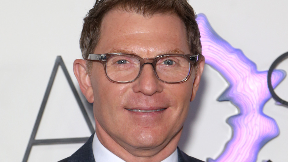 Bobby Flay wearing a gray suit and glasses