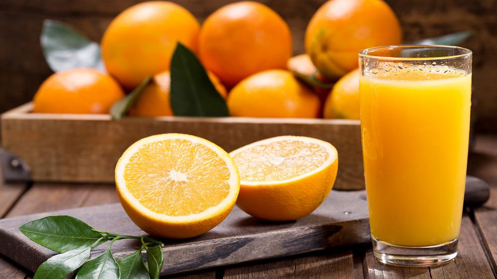 Oranges, whole and halved, next to glass of orange juice