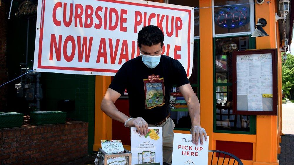 Man preparing restaurant curbside station