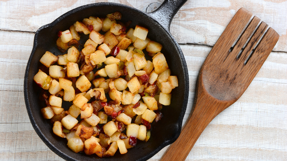 Breakfast potatoes being cooked in a cast iron skillet