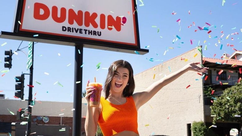 Charli D'Amelio standing outside Dunkin' with her signature drink