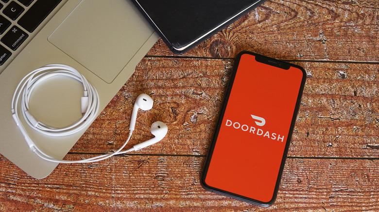 DoorDash app on phone next to laptop and headphones