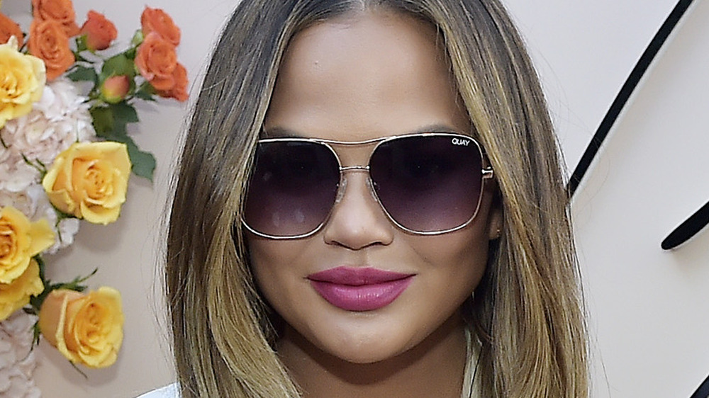 Chrissy Teigen wearing sunglasses next to flowers