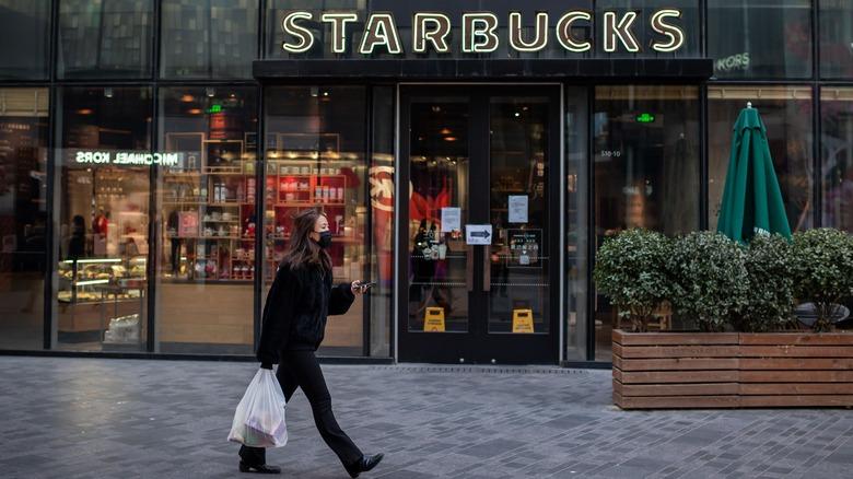 Woman in mask passes Starbucks