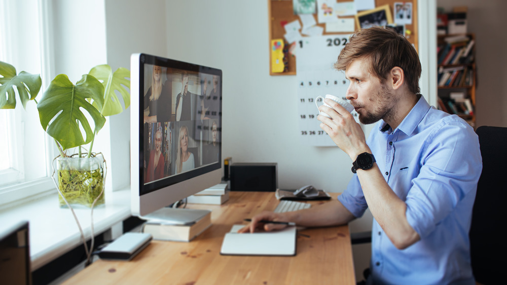 Man drinking coffee while working