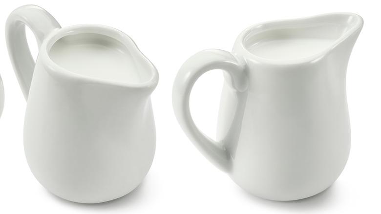 Two white creamer jars full of dairy