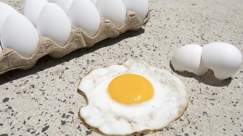 Carton of eggs cooking on sidewalk