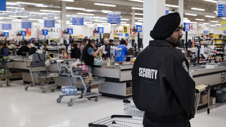security guard standing in front of cash registers