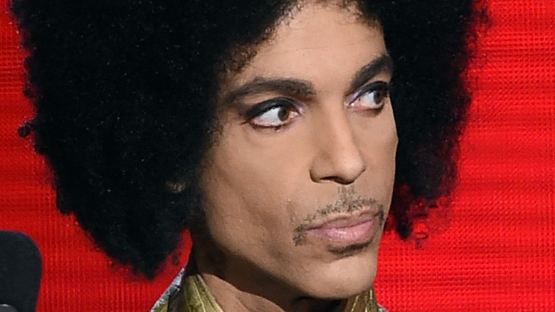 Prince, looking off-camera with a red background