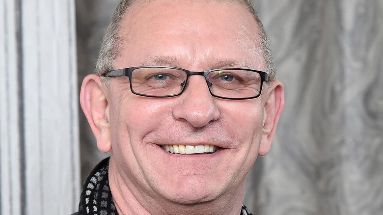 Robert Irvine smiling with black glasses
