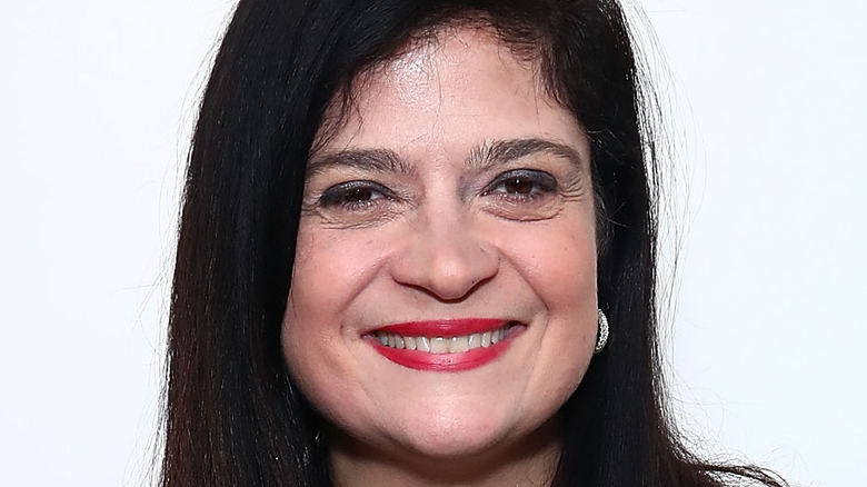 Alex Guarnaschelli wearing red lipstick and smiling