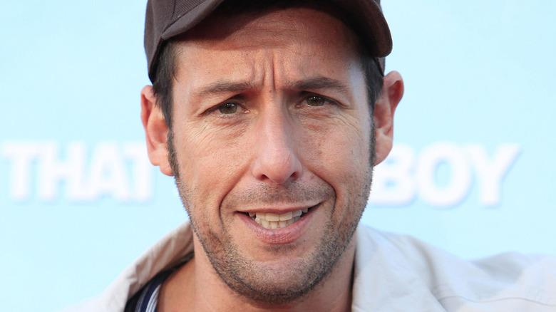 Adam Sandler wearing a baseball cap