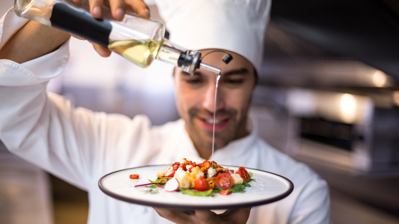 Chef drizzling dish with olive oil