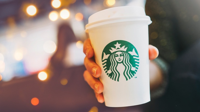 Hand holding a white Starbucks coffee cup