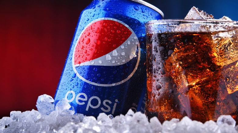 Pepsi can and glass with ice