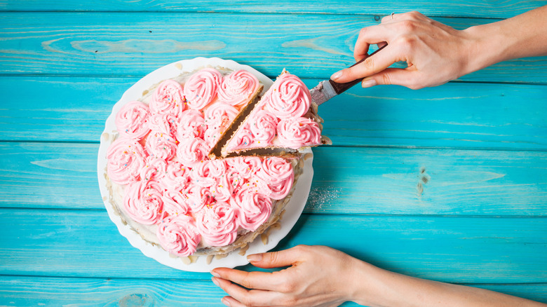Hand cutting slice of cake with swirls of pink frosting