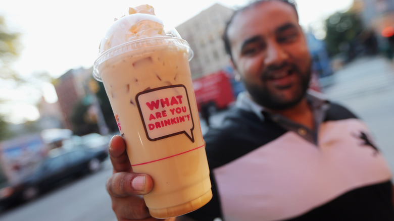 A Dunkin' drink with the branded typeface asking 'What are you drinkin'?'