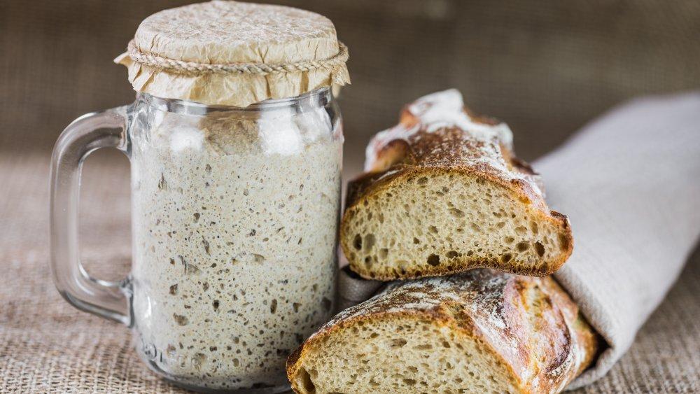 sourdough starter in jar with sourdough bread