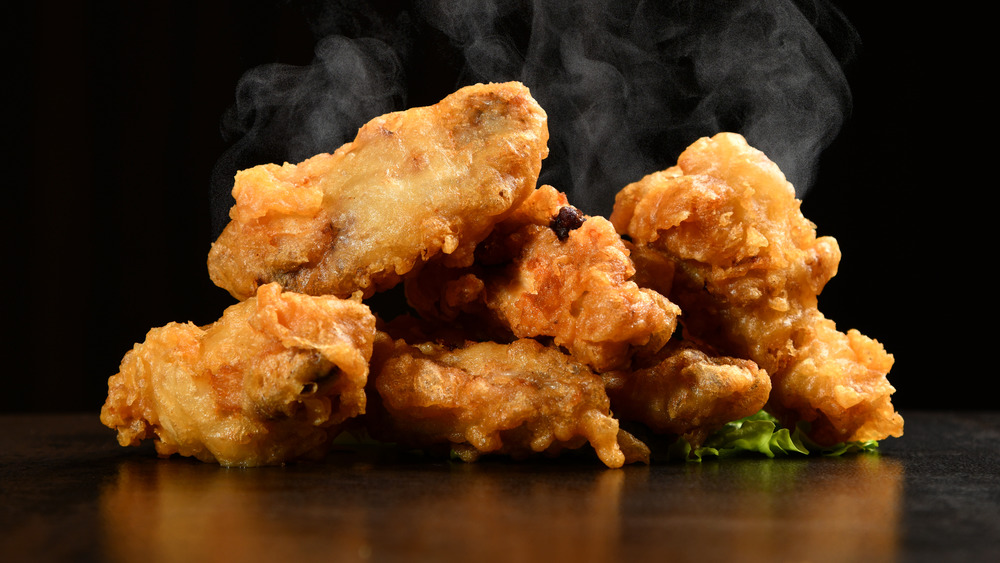 Steaming hot fried chicken on black background