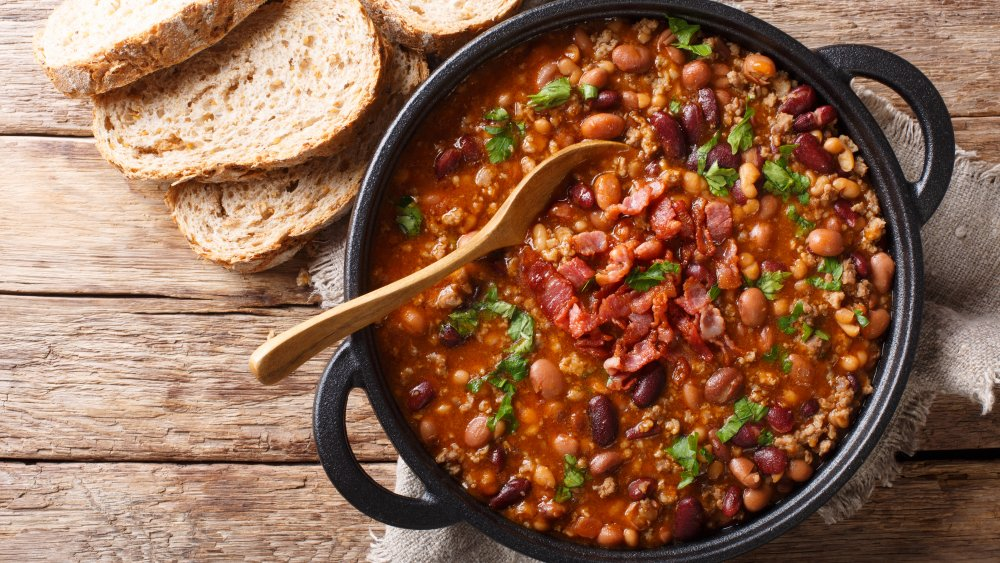 A pot of crock Crock Pot with beans and bacon inside and a serving of bread for dipping besides it.