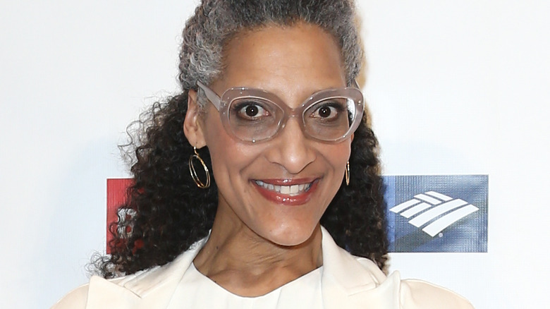 Carla Hall smiles with large-framed glasses