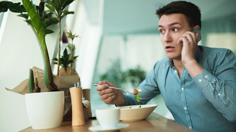 Man talking on phone while eating