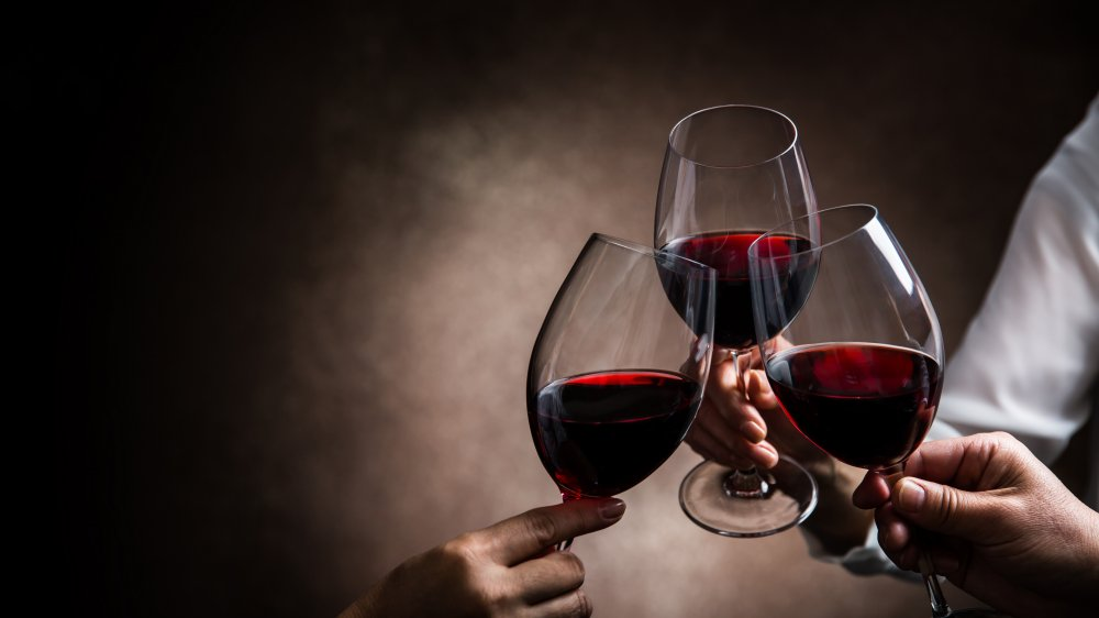 three glasses of wine in a toast