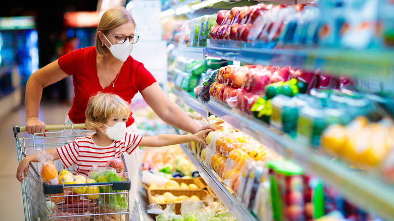 Woman and child in masks shopping at the grocery store