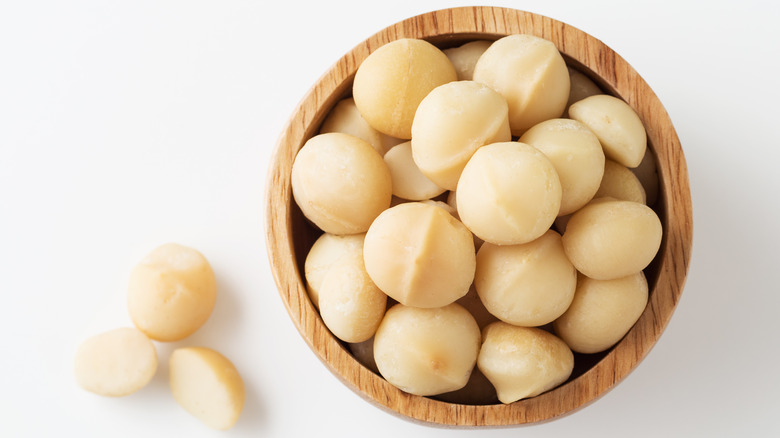 Shelled macadamia nuts in wooden bowl
