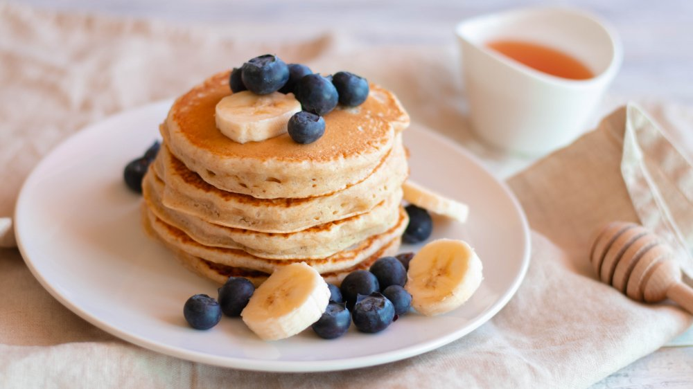 stack of pancakes topped with blueberries and banana slices