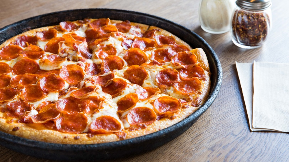 Pepperoni pizza in a pan on a table