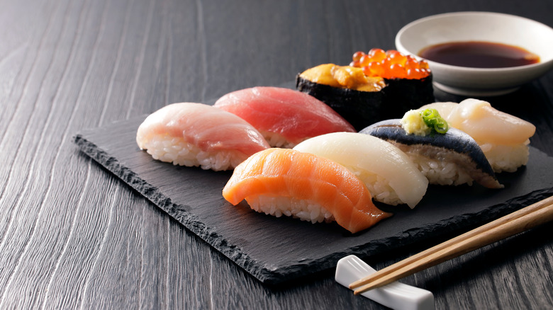 Types of sushi on a black platter