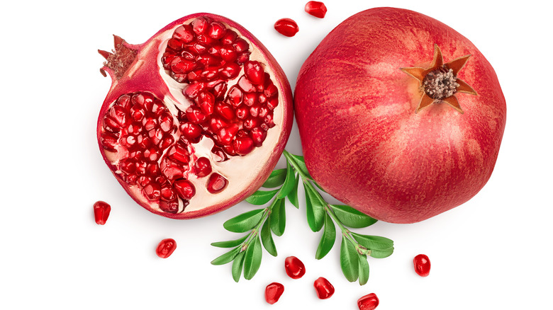 Pomegranate with seeds on white background