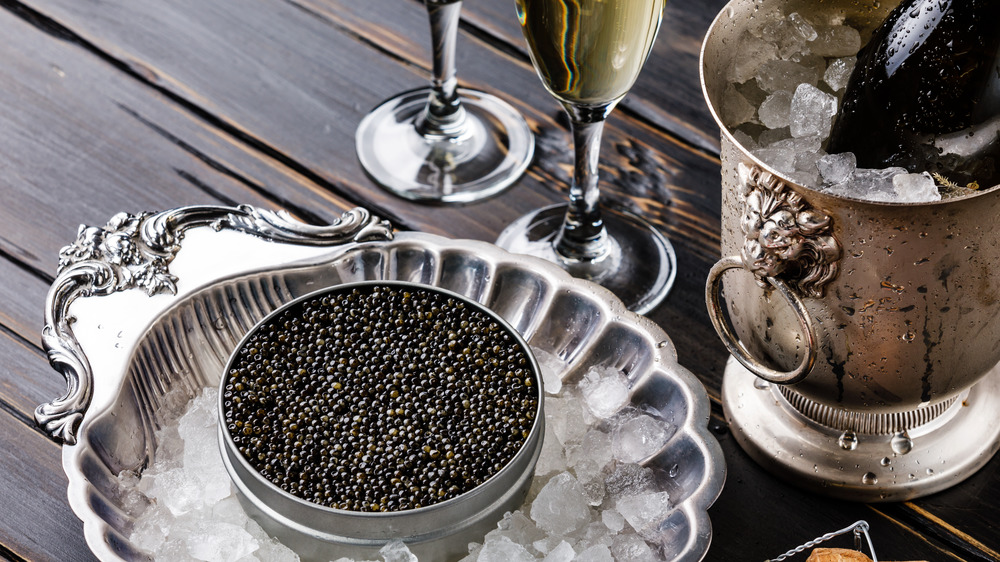 Tin of caviar on ice next to champagne bucket and two glasses of champagne