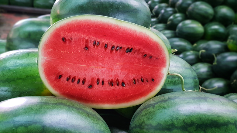 Cut watermelon stacked on whole watermelon