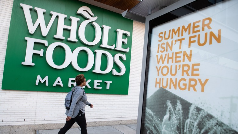 A woman walks past a Whole Foods