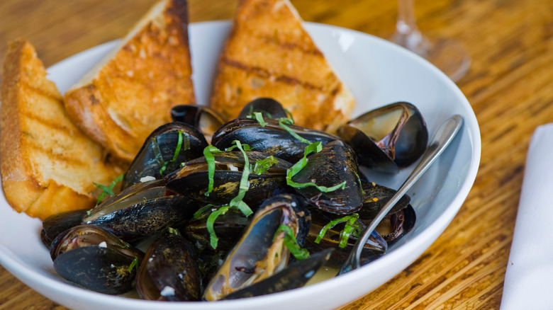 Cooked mussels in a white bowl