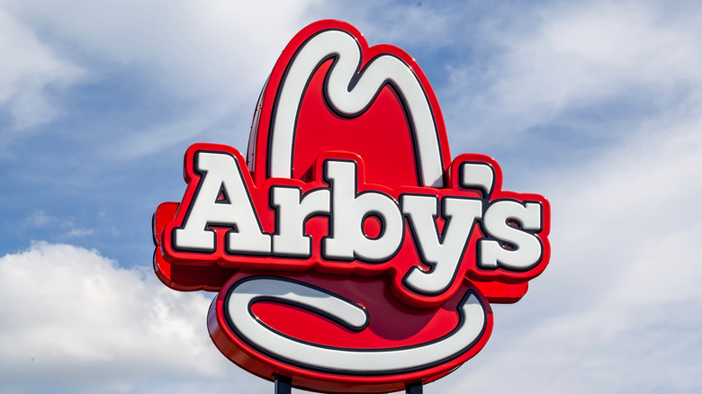 Red and white Arby's logo against blue sky