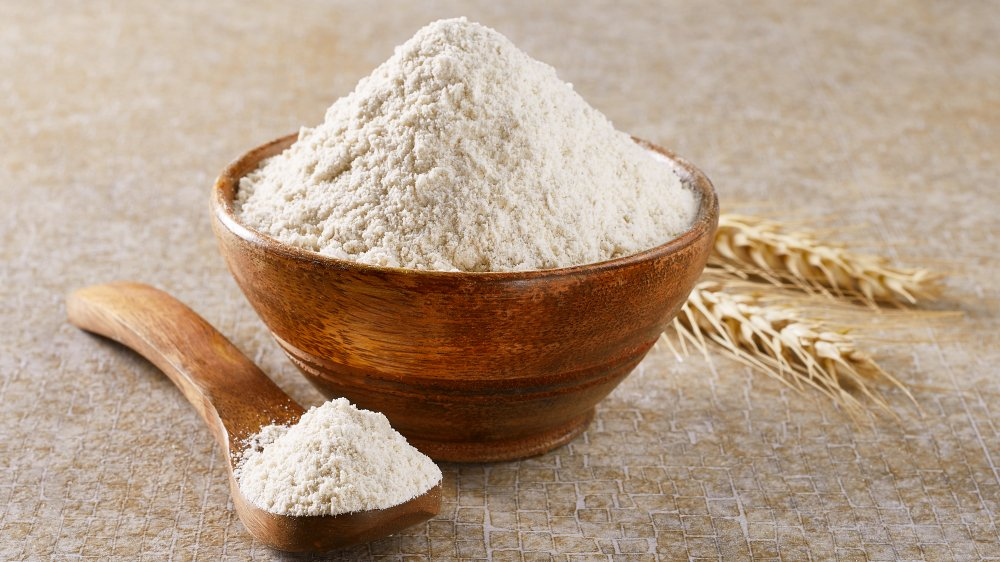 Bowl of flour with spoon filled with flour
