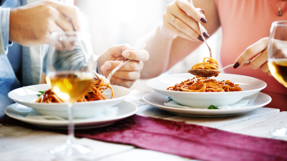 Couple in a restaurant eating spaghetti