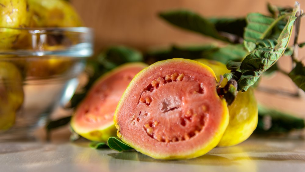 Halved guava fruit pink flesh and a yellow-green skin.