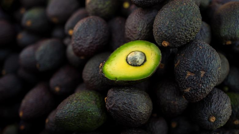 A bisected avocado lies upon its unharmed brethren.