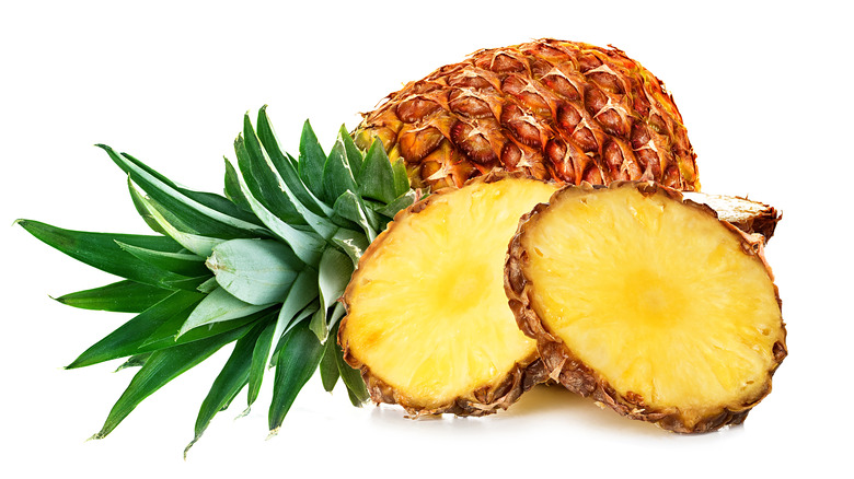 A whole pineapple next to cut up round slices