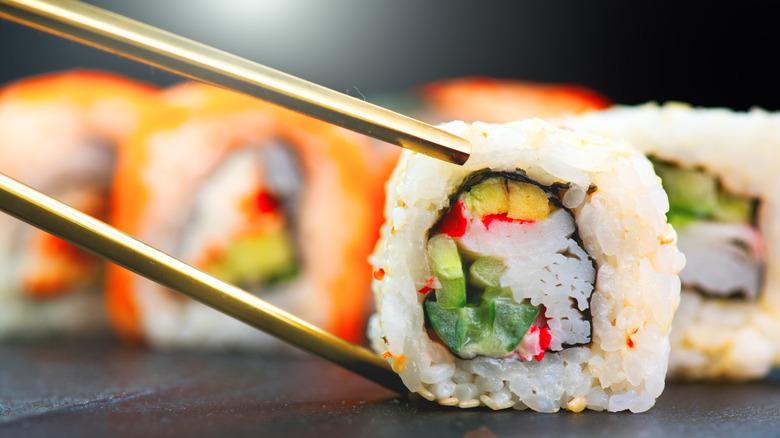 Chopsticks picking up sushi roll