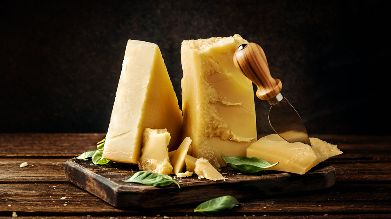 Blocks of parmesan cheese on a wooden board with basil leaves
