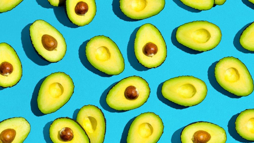Avocados sliced open revealing avocado pit