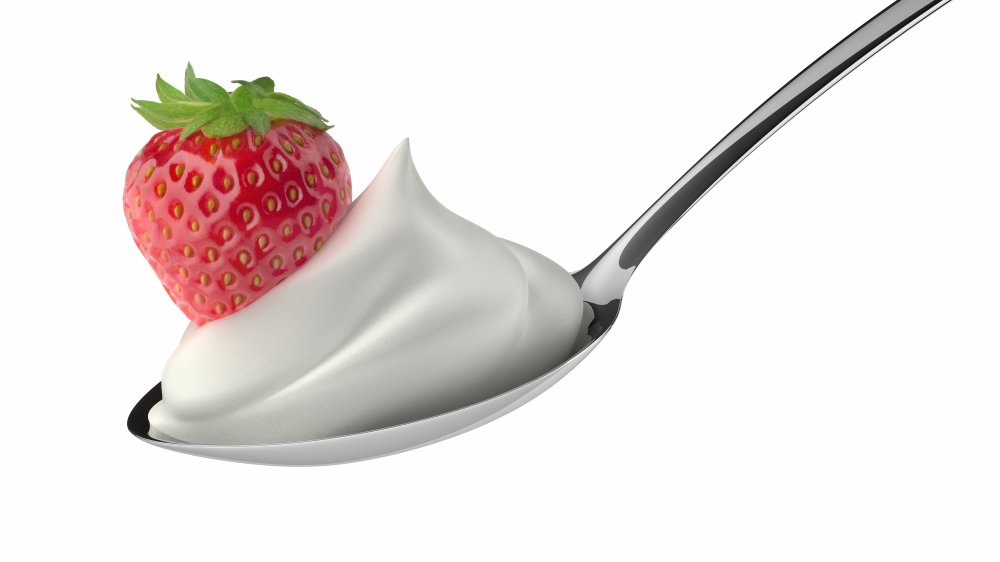 Cool whip whipped topping on a spoon with a strawberry