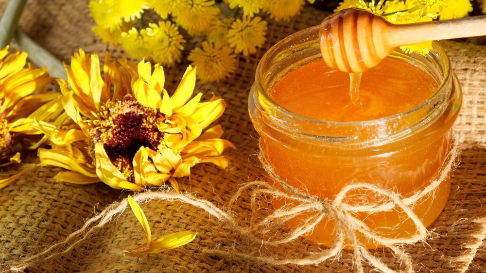 honey dripping into a jar with flowers on the side