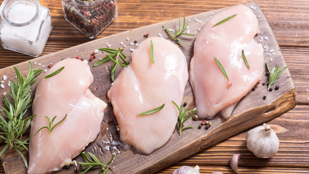 raw boneless chicken breasts on cutting board