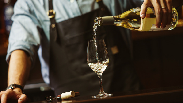 Sommelier pouring white wine